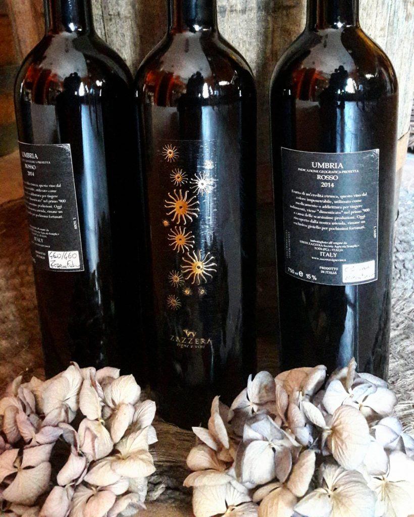 Tre bottiglie di Grero Zazzera, con in primo piano le etichette fronte e retro. In basso delle ortensie decorative