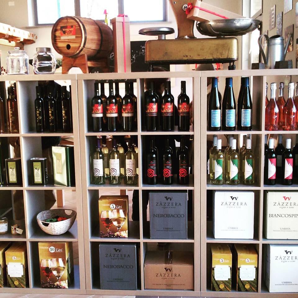 Scaffalatura piena di vini sfusi e in bottiglia, latte d'olio, prodotti in vasetto e oggetti legati al bere (calici, una piccola botte)