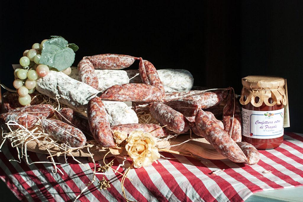 Composizione su una tavola a righe con salami e salsicce secche adornata con un grappolo d'uva e un fiore; a fianco un vasetto di confettura di fragole