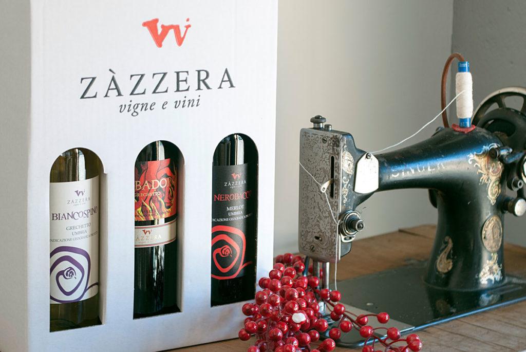 Scatola di cartone contenente tre vini Zazzera: Biancospino, Barbadoro e Nerobacco. Vicino alla scatola una vecchia macchina da cucire Singer e delle finte bacche decorative