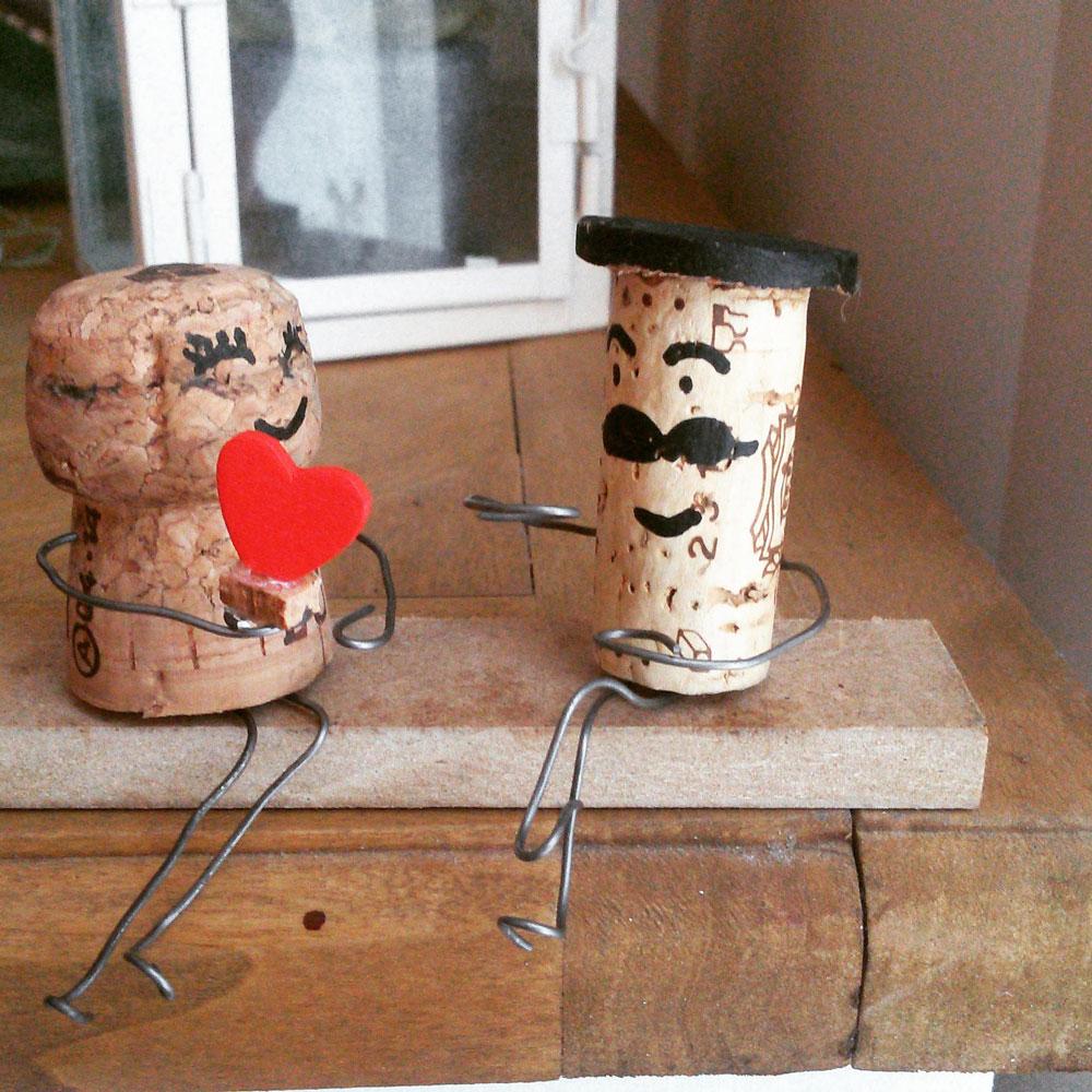 Opera creativa in legno, fil di ferro e tappi di sughero raffigurante una coppia innamorata