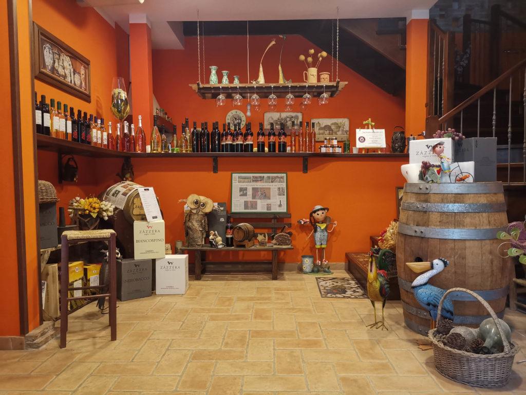 Ingresso della cantina, con i vini Zazzera esposti sul bancone, sedute per la degustazione ed elementi decorativi particolari (fiori di campo, vasi, gufo di legno, piccole statue di animali e persone)